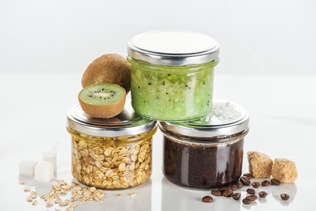 glass jars with homemade cosmetics, kiwi and brown sugar cubes on white surface Фото со стока