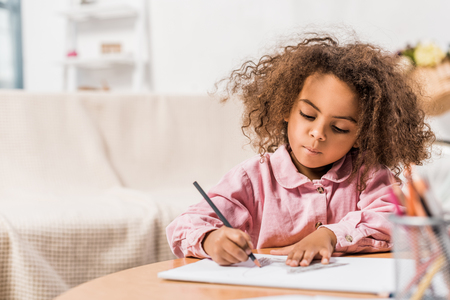 serious african american kid drawing on paper with color pencil in living room Stock Photo