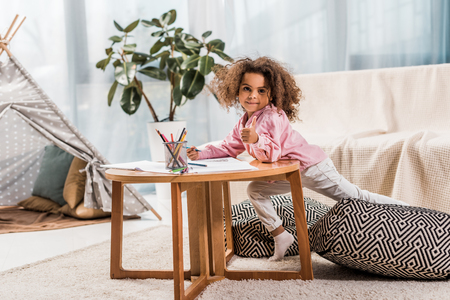 african american child drawing and showing thumb up in living room