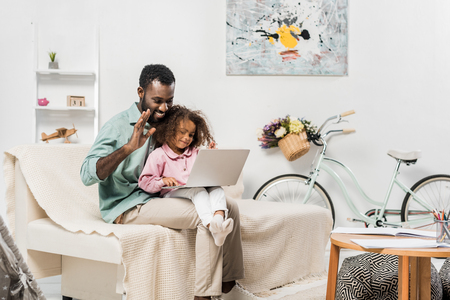 african american family using laptop in living room Фото со стока