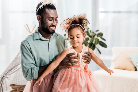 happy smiling african american father lifting up daughter in pink dress