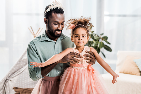 happy smiling african american father lifting up beautiful daughter in pink dress Stockfoto