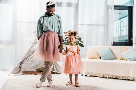 happy african american father and adorable daughter dancing in pink tutu skirts Foto de archivo - 117908660