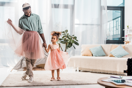 happy african american father in cute pink tutu and adorable daughter in beautiful dress Foto de archivo - 117908662