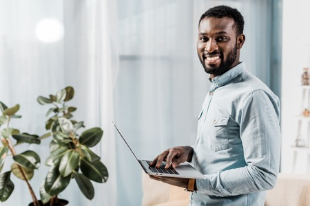 african american freelancer smiling and holding laptop 免版税图像 - 117878382