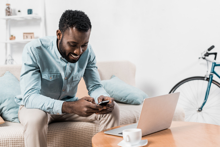 african american freelancer sitting on couch and typing on smartphone