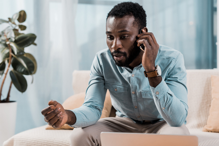 worried african american man talking on smartphone at home