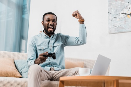 african american man rejoicing while playing video game Banco de Imagens