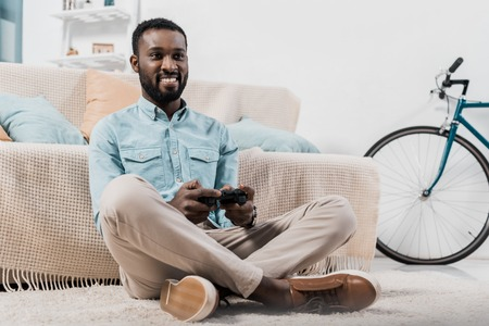 african american man sitting with crossed legs on floor and playing video game