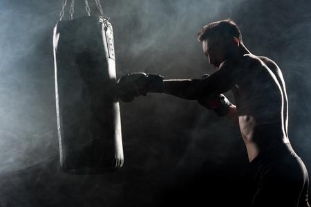 silueta, de, atleta, en, guantes de boxeo, golpear, saco de boxeo, en, negro, con, humo