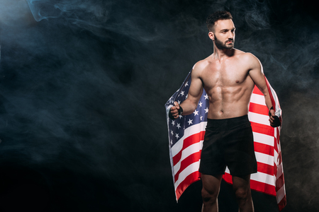 handsome shortless man holding american flag on black with smoke Stok Fotoğraf