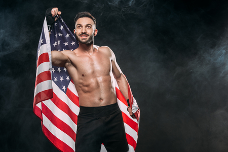 happy athlete holding american flag on black with smoke