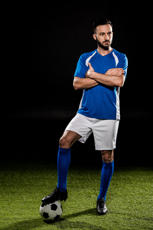 bearded football player standing with ball with crossed arms isolated on black