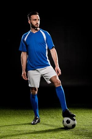 giocatore di football barbuto in piedi con la palla sull'erba isolata su black