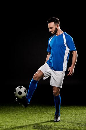 uomo barbuto che gioca con la palla sull'erba isolata sul nero