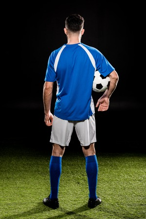 back view of sportsman holding ball and standing on grass isolated on black Фото со стока