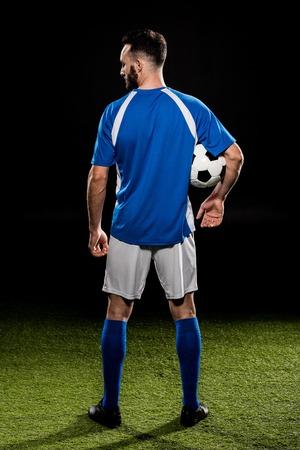 sportivo muscolare in uniforme che tiene palla isolata su black
