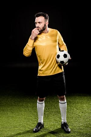 Guapo entrenador barbudo que sopla el silbato mientras sostiene la bola aislado en negro
