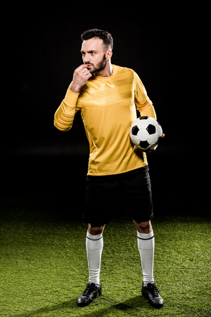 handsome bearded coach blowing whistle while holding ball isolated on black