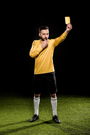handsome referee standing on grass and showing yellow card while blowing whistle isolated on black