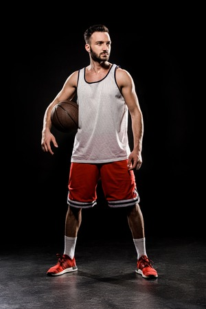 muscular basketball player standing with ball on black background Фото со стока