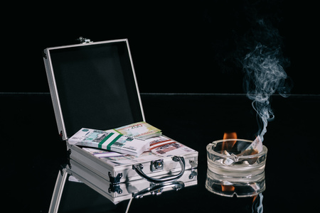 russian rubles banknotes in suitcase safe box and burning money in ashtray on black Imagens
