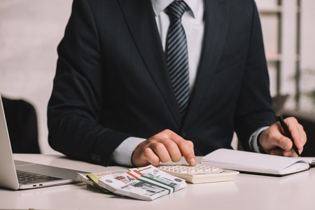 cropped shot of businessman using calculator and taking notes in notepad at workplace with laptop and russian rubles banknotes Reklamní fotografie