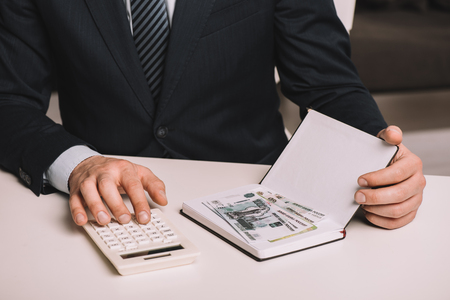 cropped shot of businessman using calculator and holding notebook with russian rubles banknotes
