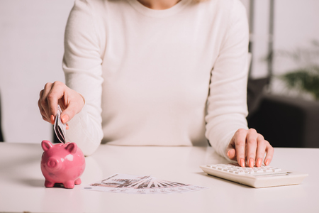 mid section of woman using calculator and putting russian rubles into piggy bank Reklamní fotografie