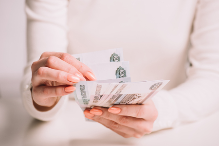 cropped shot of woman counting russian rubles banknotes, selective focus Stockfoto