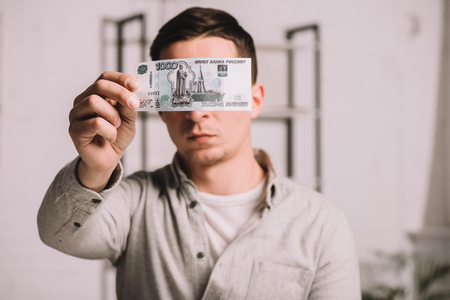 young man hiding face behind russian rubles banknote Imagens