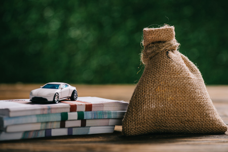 close-up view of sackcloth bag with money, rubles banknotes and model car on wooden table