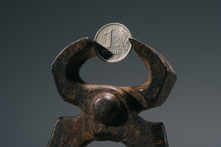 close-up view of iron vise tool with one ruble coin isolated on grey