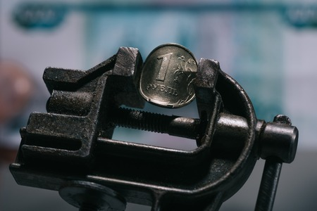 close-up view of iron vise tool with one ruble coin, selective focus Imagens