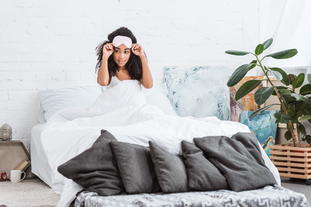 young african american woman with blindfold on forehead sitting in bed during morning time at home