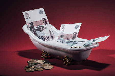 russian rubles banknotes in small tub and coins on red, money laundering concept Imagens