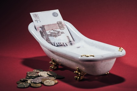 close-up view of russian rubles in small tub and coins on red, money laundering concept