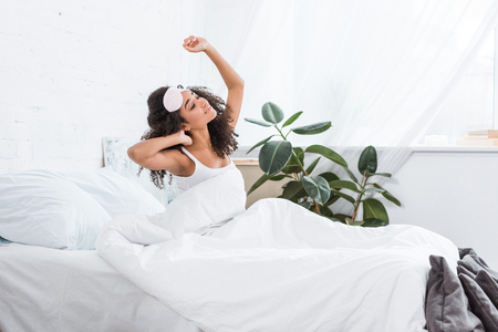 side view of young african american woman with blindfold on forehead stretching in bed during morning time at home Standard-Bild