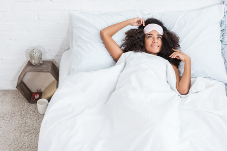 high angle view of young african american woman with blindfold on forehead in bed during morning time at home
