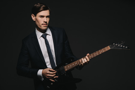 confident businessman playing elecrtonic guitar isolated on black