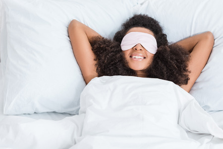 happy african american girl with eyes covered by sleeping blindfold in bed during morning time at home
