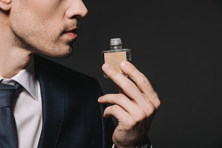 cropped view of man in suit smelling perfume isolated on black 写真素材