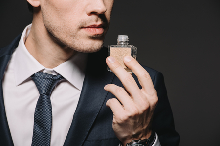 cropped view of businessman smelling perfume isolated on black