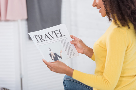partial view of smiling girl reading travel newspaper at home