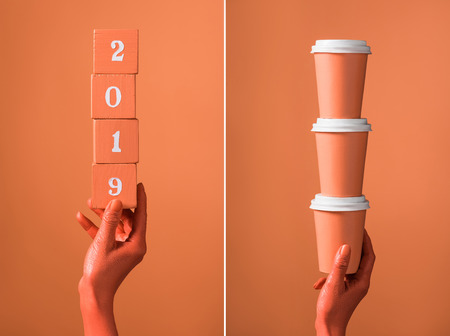 coral wooden cubes with 2019 numbers and stack of coral paper cups in female hands on divided coral background, color of 2019 concept