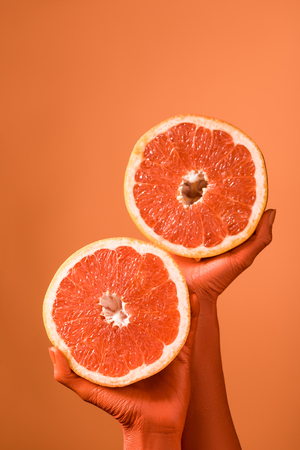partial view of coral colored female hands with grapefruit halves on coral background, color of 2019 concept Stock Photo
