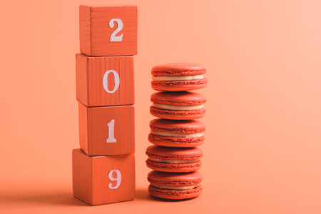 stack of wooden cubes with 2019 numbers and macarons on coral background, color of 2019 concept