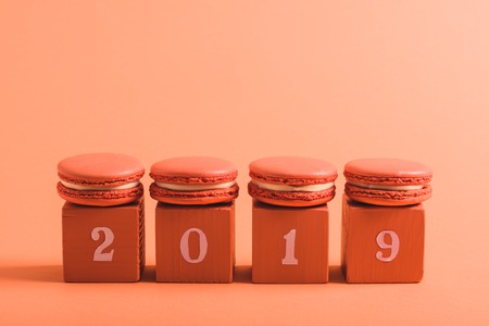 coral cubes with 2019 numbers and macarons on coral background, color of 2019 concept Banco de Imagens