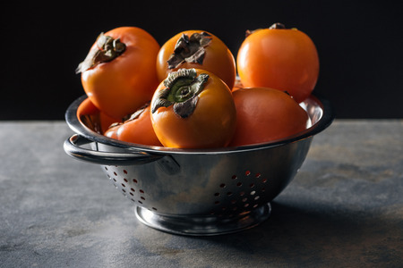 orange and whole persimmons in colander isolated on black