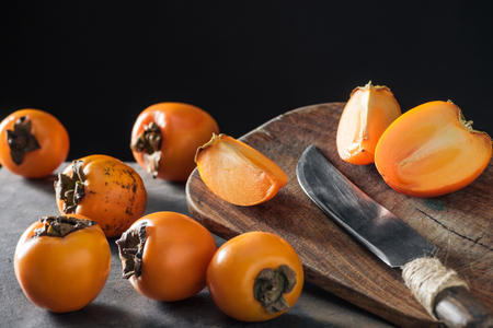 ripe and orange persimmons on cutting board with knife